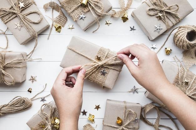 Kobieta dekorowanie prezentów świątecznych pudełko. leżał płasko