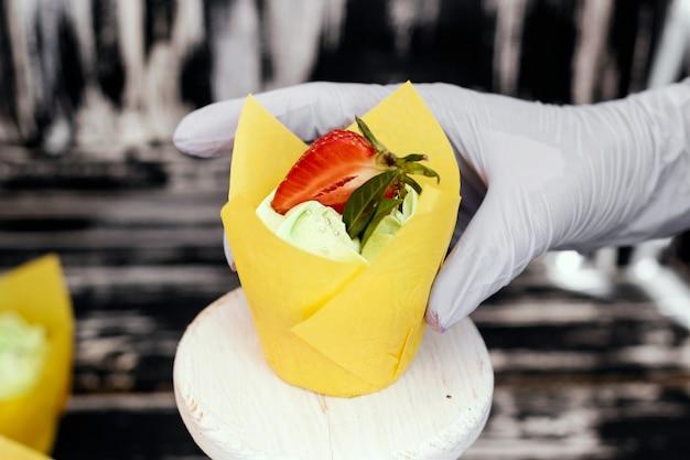 Kobieta dekoruje babeczki truskawkowe. zdjęcie procesu. domowe babeczki.