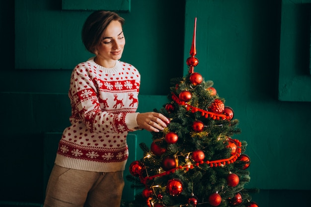 Kobieta dekoruje choinki z czerwonymi zabawkami
