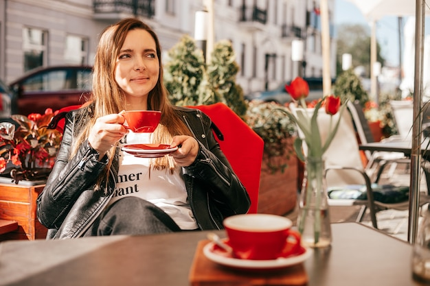 Kobieta delektująca się kawą przy stole europejskiej kawiarni ulicznej, uśmiechnięta i odwracająca wzrok
