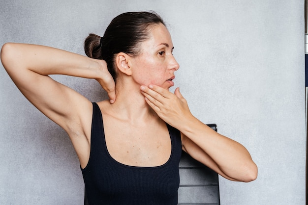 Kobieta delikatnie obraca głowę obiema rękami podczas wykonywania ćwiczeń karku metodą mckenzie, łagodzących ból szyi
