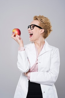 Kobieta dentysta gryzie pyszne jabłko