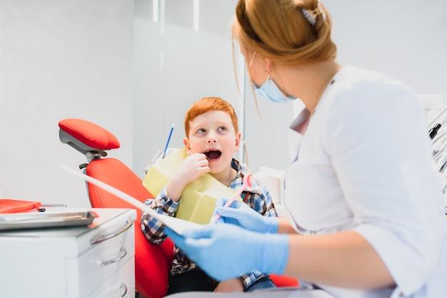 Kobieta dentysta i dziecko w gabinecie dentystycznym