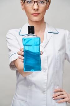 Kobieta dentysta lekarz trzymając butelkę płynu do płukania jamy ustnej