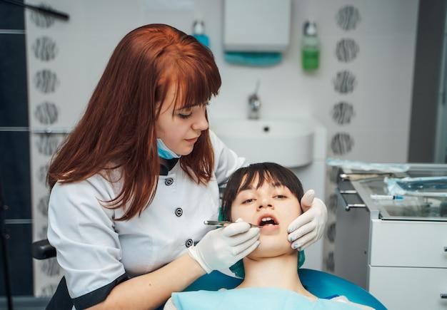 Kobieta dentysta pracuje przy jej pacjentów zębami.