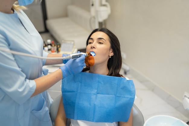 Kobieta dentysta w klinice stomatologicznej, która prowadzi badanie i leczenie jamy ustnej pacjentki