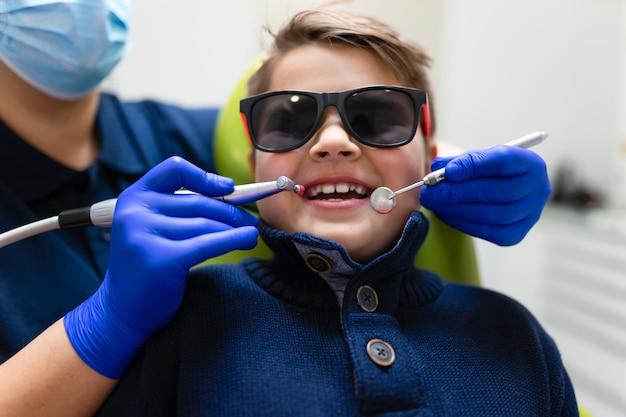 Kobieta dentysta wykonuje profilaktyczne czyszczenie płytki nazębnej