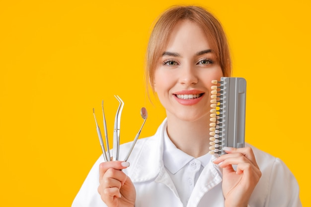 Kobieta dentysta z narzędziami i kartą kolorów zębów na żółtej powierzchni