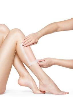 Kobieta depilująca nogi woskiem