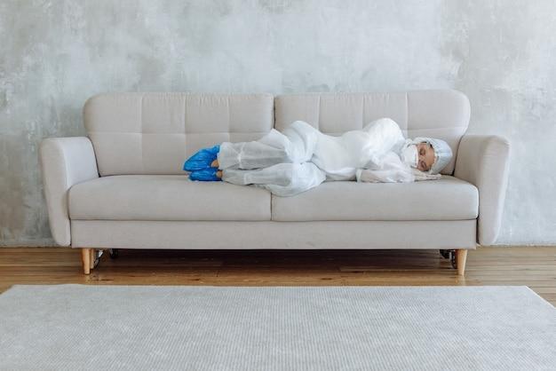 Kobieta dezynfektor w białych rękawiczkach kombinezonu i respiratorze odpoczywająca lub śpiąca na kanapie