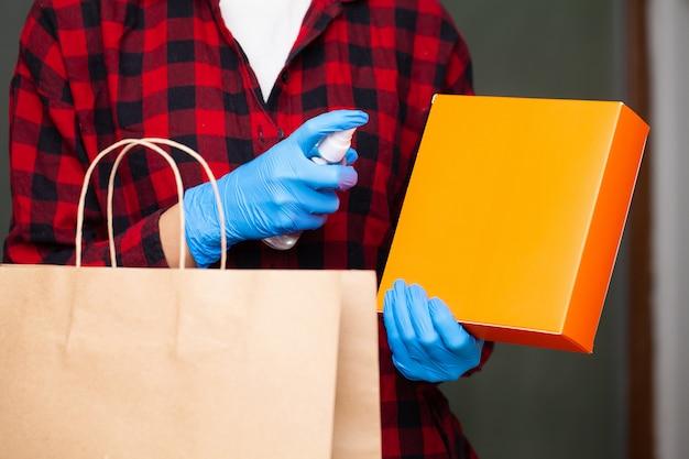 Kobieta dezynfekuje paczki przed rozpakowaniem w domu