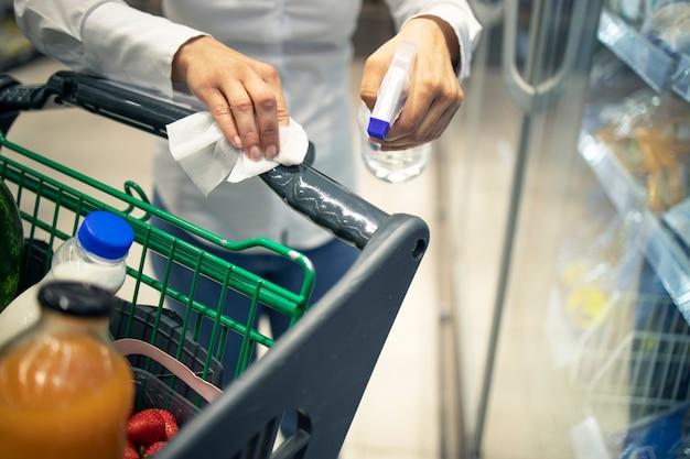 Kobieta dezynfekuje wózek sklepowy środkiem dezynfekującym przed użyciem z powodu pandemii wirusa koronowego.