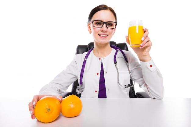 Kobieta dietetyka siedzi w swoim miejscu pracy, pokazując i oferując szklankę soku pomarańczowego świeżego soku pomarańczowego w ręku