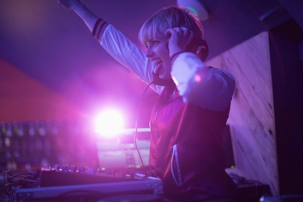 Kobieta dj zabawy podczas odtwarzania muzyki w barze