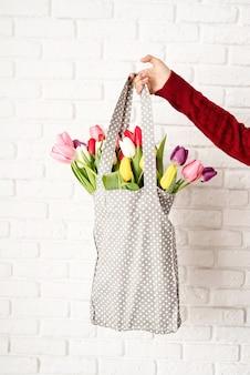 Kobieta dłoń trzymająca worek z szarej tkaniny w kropki z kolorowymi tulipanami