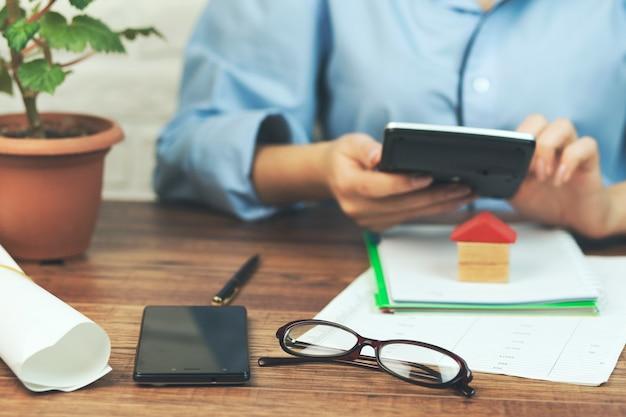 Kobieta dłoni kalkulator w biurze