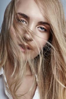 Kobieta długie włosy blondynka macha na wietrze