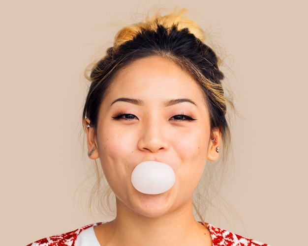 Kobieta dmuchająca gumą do żucia, portret wesołej twarzy