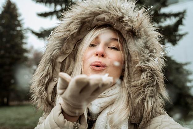 Kobieta dmuchająca w śnieg z jej ręki