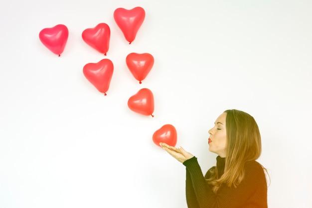 Kobieta dmuchanie balonã³w serca