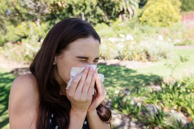 Kobieta dmuchanie nosa z bibuły