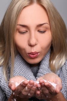Kobieta dmuchanie płatki śniegu z jej ręki