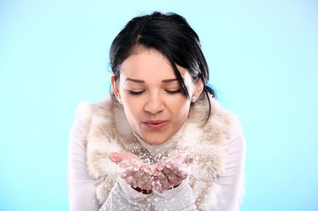 Kobieta dmuchanie płatki śniegu