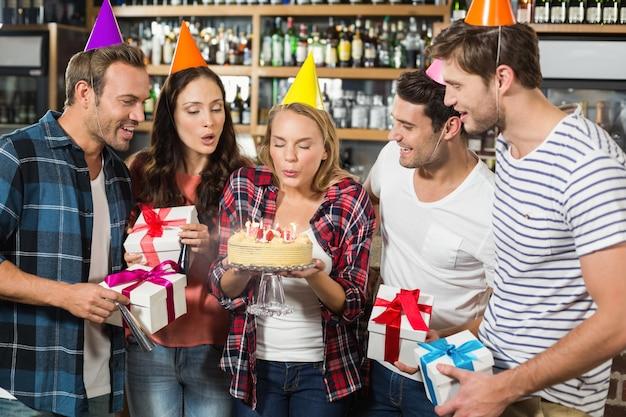 Kobieta dmuchanie świeczki, podczas gdy przyjaciele oglądać