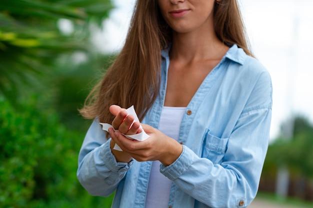 Kobieta do czyszczenia i dezynfekcji rąk antybakteryjnymi mokrymi chusteczkami na zewnątrz
