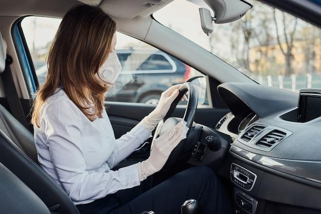 Kobieta do czyszczenia samochodu sprayem dezynfekcyjnym w celu ochrony przed koronawirusem