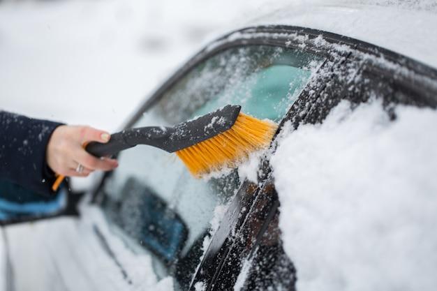 Kobieta do czyszczenia śniegu z samochodu zimą