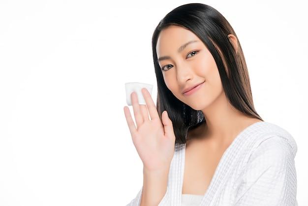 Kobieta do pielęgnacji skóry usuwa makijaż twarzy za pomocą wacika bawełnianego.