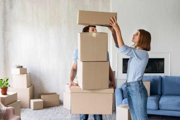 Kobieta dodaje pudełko na stos, które jej partner trzyma, aby się wyprowadzić