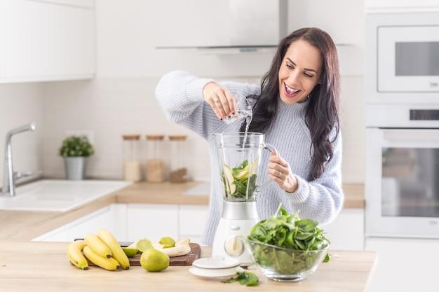 Kobieta dodaje wodę do miksera na smoothie ze szpinaku, banana i jabłka.