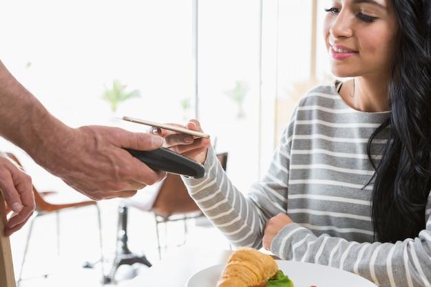 Kobieta dokonująca płatności za pośrednictwem nfc