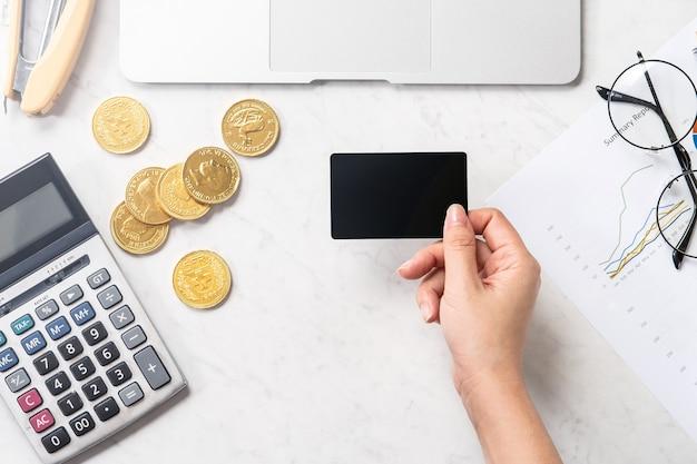 Kobieta dokonuje płatności online za pomocą karty i smartfona odizolowanych na nowoczesnym marmurowym stole biurowym
