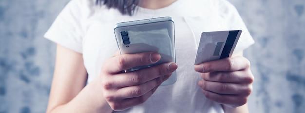 Kobieta dokonuje płatności przez telefon kartą na szarym tle
