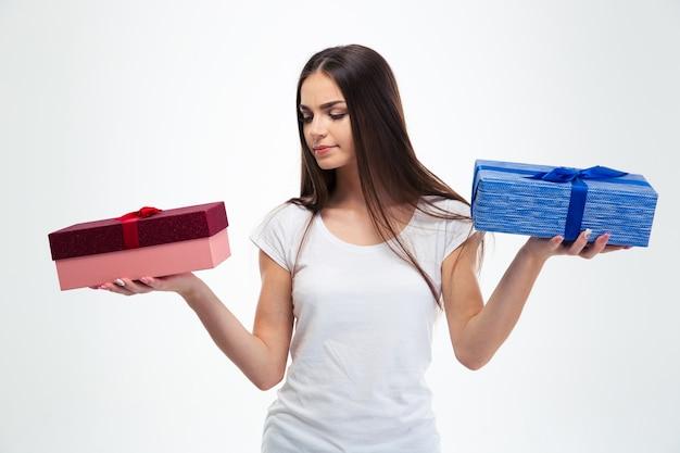 Kobieta dokonuje wyboru między dwoma pudełkami na prezent