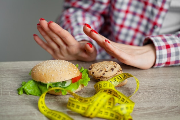 Kobieta dokonuje wyboru między szkodliwą a zdrową żywnością
