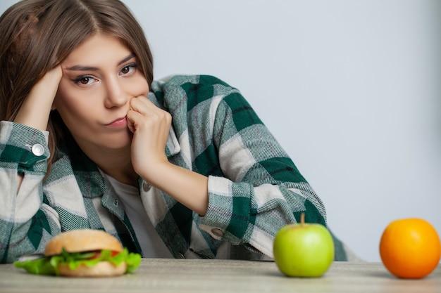 Kobieta dokonuje wyboru między zdrową a szkodliwą żywnością