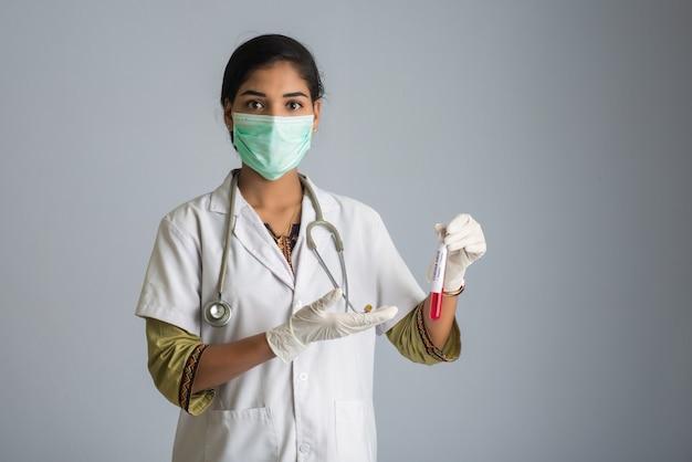 Kobieta doktor trzymając probówkę z próbką krwi do koronawirusa lub analizy 2019-ncov.