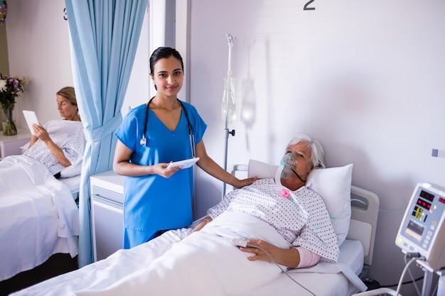 Kobieta doktorski pocieszający żeński starszy pacjent