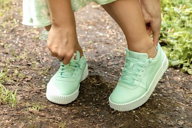 Kobieta dopasowuje tenisówki, kiedy pociera jej stopy