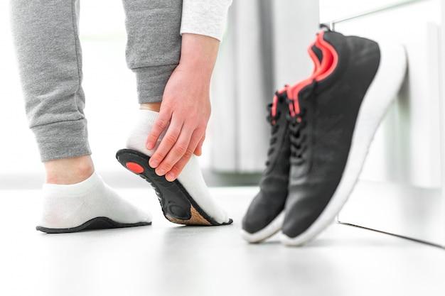 Kobieta dopasowuje wkładki ortopedyczne. leczenie i zapobieganie chorobom płaskich stóp i stóp. pielęgnacja stóp, komfort stóp. opieka zdrowotna. noszenie wygodnych butów sportowych
