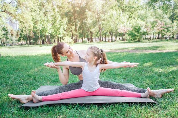 Kobieta dorastająca i dziecko siedzą na pozycji sznurka. to jest dla nich bardzo łatwe. mała dziewczynka trzyma ręce na boku i poziomo, podczas gdy mama trzyma ręce.