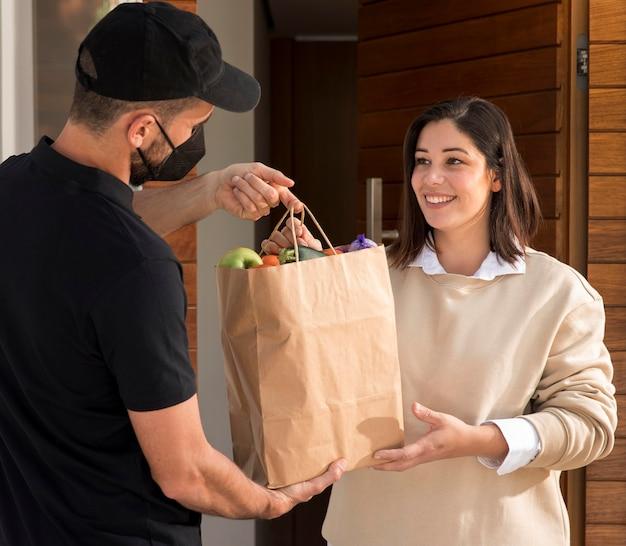 Kobieta dostaje dostarczoną torbę z jedzeniem