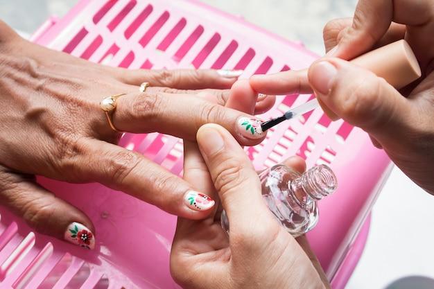 Kobieta dostaje gwoździa manicure