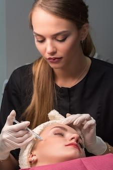 Kobieta dostaje kosmetyczny zastrzyk botulinowy na twarz. zabieg odmładzający i nawilżający.