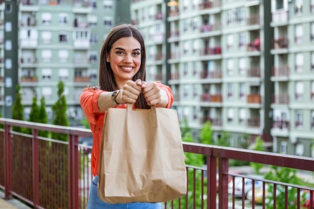 Kobieta dostarcza jedzenie w papierowej torbie. kurier dostarczył zamówienie bez nazwy torby z jedzeniem.
