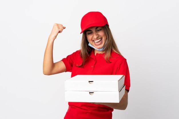 Kobieta dostarczająca pizzę trzymająca pizzę i chroniąca przed koronawirusem z maską na odosobnionej białej ścianie świętująca zwycięstwo